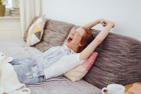 Relaxed young woman relaxing on a day bed with a rug over her legs stretching her arms and yawning widely Foto de archivo