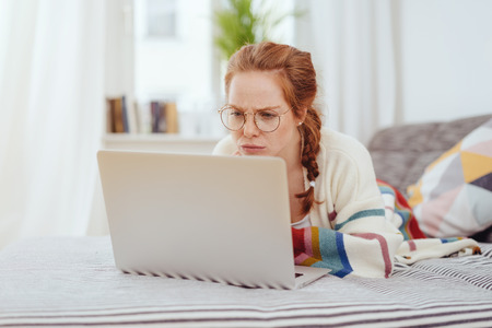 Confused young woman frowning at her laptop as she relaxes on her bed working in a close up view Stock Photo