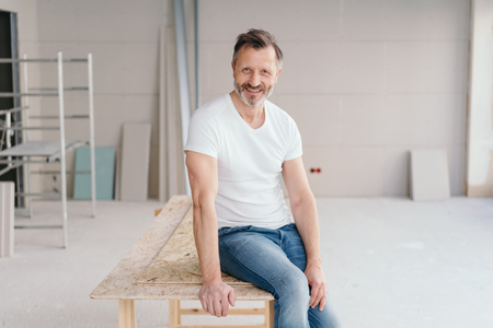 Handyman or homeowner inside a new build house sitting perched on the edge of a trestle work table smiling at the camera