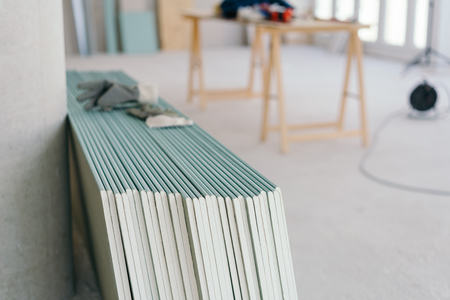 White chip board stacked against the wall inside a new build house with work table visible in the background in a spacious room Stok Fotoğraf
