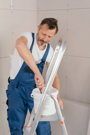 Painter or handyman in denim overalls mixing paint in a tub on an aluminum stepladder in a corner angle with new unpainted wall cladding Imagens