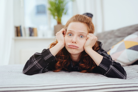 Exasperated young woman pulling a funny face resting her head in her hand as she lies on her stomach on a bed