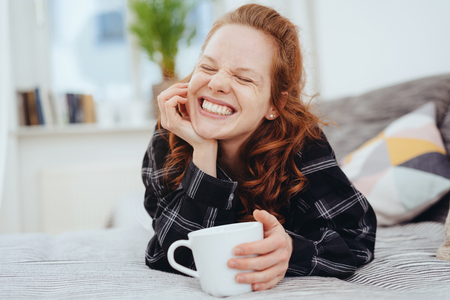 Happy young woman grinning happily with closed eyes as she enjoys a mug of coffee on a day ben at home