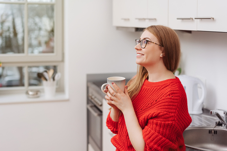 Happy young woman standing daydreaming as she stands in the kitchen clutching a mug of coffee looking up with a smile of anticipation