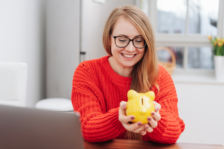 Young blond woman holding a yellow piggy bank cupped in her hands with a beaming smile as she anticipates what she can do with her savings