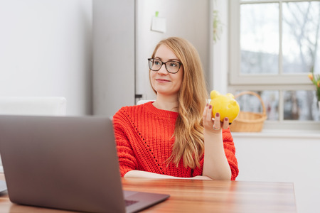Thoughtful young woman holding a yellow piggy bank as she relaxes at a table at home looking up with a smile as she imagines all the things she can do with her savings