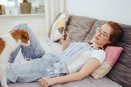 Tired young woman relaxing on a day bed with closed eyes watched by her little pet terrier dog Stock fotó