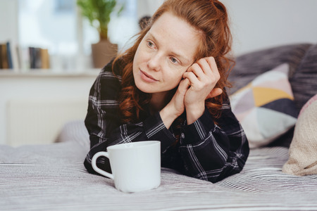 Thoughtful young woman staring aside as she relaxes on a bed with a large mug of coffee looking away with a pensive expression 版權商用圖片
