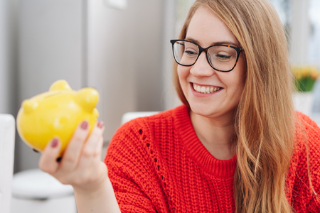Young woman looking at her piggy bank with a pleased smile as she imagines everything she can do or achieve with her savings