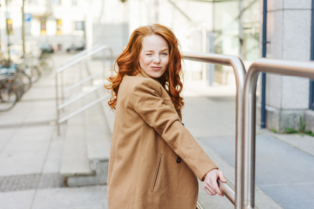 Cute charismatic young woman pulling a funny face as she stands holding a railing on a sidewalk in town looking at camera
