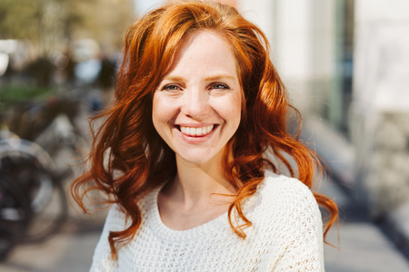 Friendly young redhead woman with a vivacious smile standing in a city street grinning at the camera in a close up portrait