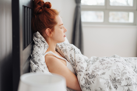 Young redhead woman relaxing sitting up in bed against the pillows with her eyes shut and sunlight coming in through the window behind 版權商用圖片