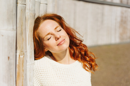 Young redhead woman soaking up the sun on her face with a blissful smile and closed eyes as she leans against an old wall Stockfoto