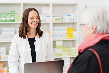 Smiling pharmacist chatting to an elderly lady in the pharmacy as she dispenses her medication
