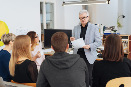 Manager or business leader talking to his team standing perched on an office table reading from a document in his hand viewed from the rear Banco de Imagens