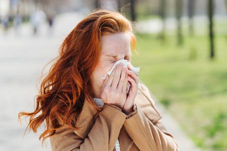 Junge Frau, die im zeitigen Frühjahr an Heuschnupfen oder Pollenallergie leidet, putzt sich im Freien in einem Park die Nase auf einem Taschentuch