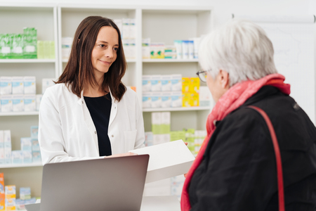 Sympathetic female pharmacist listening to an elderly woman in the pharmacy as she explains her symptoms