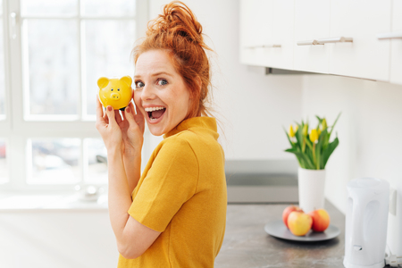 Happy young woman with yellow piggy bank in her hands, smiling at camera, standing in the kitchen. Half-turn half-length portrait Banco de Imagens