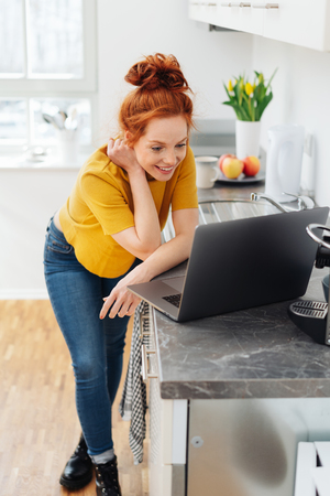 Young woman using a laptop in the kitchen leaning on a marbled grey counter reading the screen with a happy relaxed smile Imagens