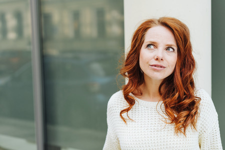 Thoughtful young redhead woman in the street in town looking up with a pensive expression as she ponders a problem