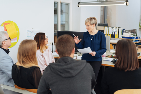 Businesswoman addressing a group of colleagues in a large open plan office as they sit grouped around in chairs viewed from the rear Foto de archivo