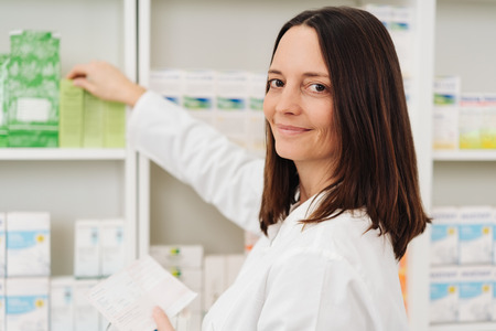 Smiling female pharmacist checking a prescription taking medication off the shelf turning to look at camera