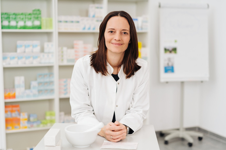 Female pharmacist at work in a pharmacy leaning on the counter looking at camera with a friendly happy smile