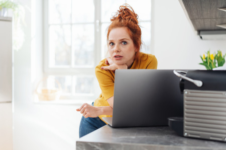 Surprised young woman staring wide eyed at camera as she leans on the edge of a kitchen counter using a laptop with high key copy space on a window Stock Photo