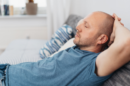 Middle-aged man relaxing with closed eyes on a comfortable sofa at home in a close up side view Banco de Imagens