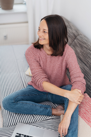 Smiling happy barefoot woman relaxing on a sofa with her feet up looking to the side with a beaming smile in a high angle view