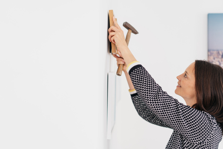 Happy woman decorating her home hanging pictures on the wall adjusting the frame with a hammer in one hand