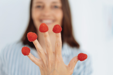Playful woman with raspberries on her fingertips holding her splayed hand on display to the camera in a selective focus view