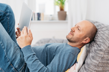 Man relaxing on a couch reading on a tablet pc with his legs up and an engrossed expression, close up side view