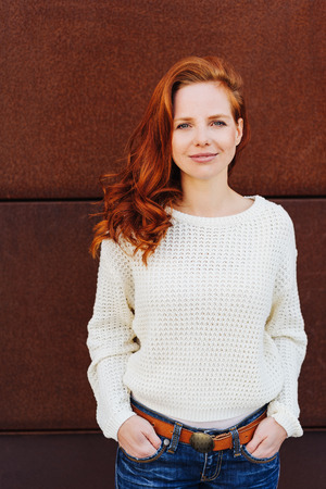 Beautiful young woman with curly red hair, wearing white knitted sweater, standing against brown wall with her hands in jeans pockets and looking at camera. Half-length front portrait Imagens