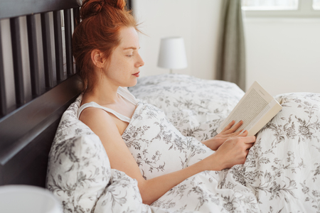 Young woman reading a book at home or in hotel room, sitting in bed covered with blanket, leaning back on dark wooden headboard Imagens