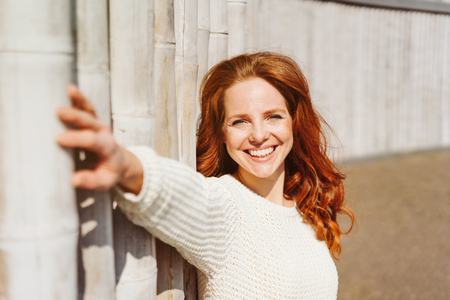 Happy vivacious young redhead woman with a beaming friendly smile leaning against an exterior wall extending her arm to the camera