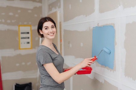 Happy attractive young woman painting a wall with a roller and colorful blue paint inside her house during renovations and redecorating