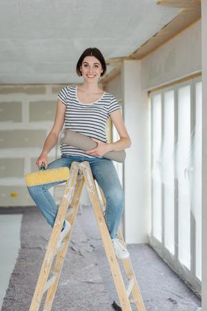 Jeune femme perchée sur un escabeau tenant un rouleau de papier peint dans une pièce partiellement achevée dans une nouvelle maison de construction