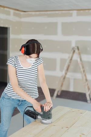 Jeune femme portant des cache-oreilles pour le ponçage du bruit des planches de bois avec une ponceuse orbitale pendant les rénovations de bricolage de sa maison Banque d'images