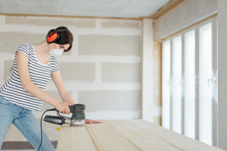 Young woman wearing ear muffs for noise and a face mask for dust using an orbital sander on planks of wood while renovating her house