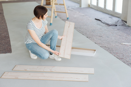 Young woman doing DIY renovations at home kneeling on the floor with planks of wood in an unfinished living room
