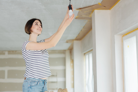 Young woman fitting a light bulb into an electrical ceiling fitting on site in a partially completed house interior with a happy smile