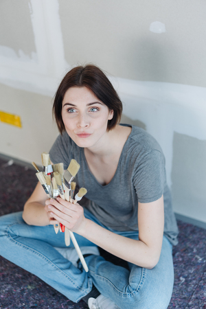 Thoughtful young woman clutching a collection of different paintbrushes in her hands as she sits on the floor in front of an unpainted wall with cladding during renovations Banque d'images