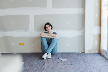 Young woman sitting on the floor in an incomplete new build or renovated house staring at the camera with a serious expression