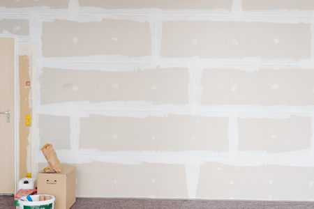 Room in a house during renovations or a new build with unpainted cladding on the walls and tools stacked in a corner
