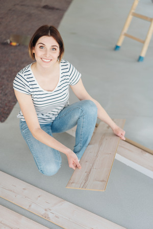 Capable young woman doing carpentry while decorating at home kneeling on the floor with wooden boards looking up with a smile