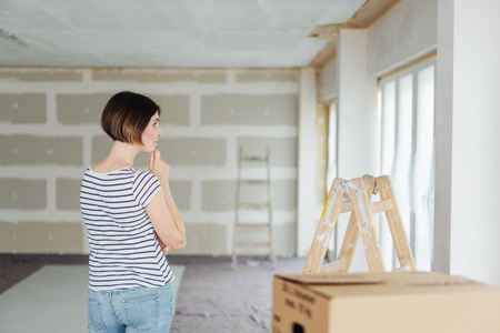 Contemplative young woman inside a new build house standing with her hand to her chin looking aside at a newly painted wall