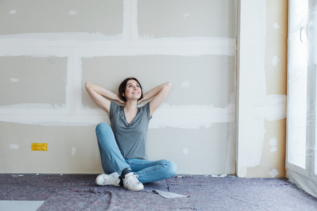 Young woman sitting on the floor on blankets leaning against an unpainted wall daydreaming about her new home with a happy smile Banque d'images