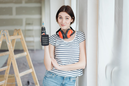 Wry young woman standing beside a ladder in a new home holding a power drill and pulling a comical face Banque d'images