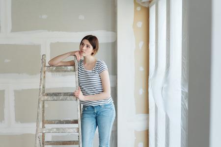 Jeune femme réfléchie lorgnant sur les rénovations en cours dans le salon de sa maison alors qu'elle s'appuie sur un escabeau avec une expression contemplative